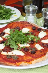Pizza with ricotta cheese, olives and rocket salad