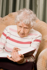 The elderly woman reads the book
