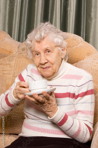 Grandmother from coffee on a sofa