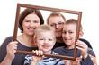 Familie schaut durch leeren Bilderrahmen
