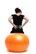 junge frau mit rückenschmerzen sitzt auf einem gymnastikball