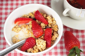 Breakfast cereal with strawberries and a cup of tea