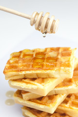 delicious Belgian waffles and stick to honey isolated on white