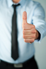 Young business man showing thumb up