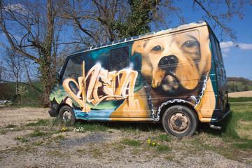 Graffiti d'un chien sur un vieux véhicule.