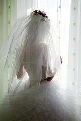 Bride silhouette looking through window