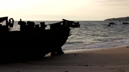 Stranded fishing boat silhouette in a desert beach with waves