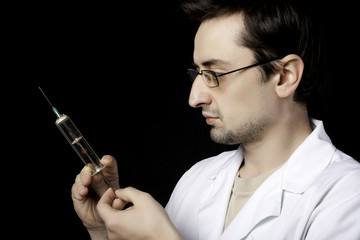 Doctor measuring liquid in syringe