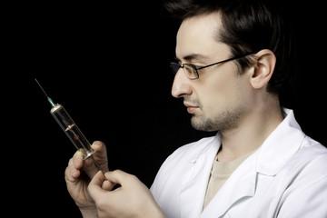 Doctor measuring liquid in syringe