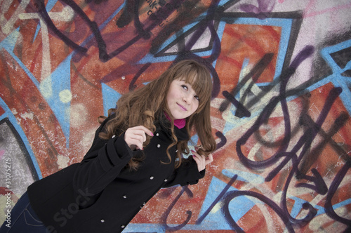 The young girl on a background of a wall with graffiti