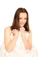 Junge Frau versteckt sich hinter Bettwäsche