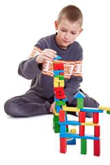 Junge baut vorsichtig einen Turm