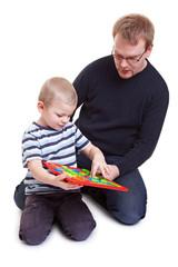 Mann und Kind spielen mit Magnettafel