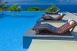 lits de soleil en bois en bordure de piscine à débordement