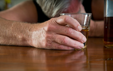 alcoholism - lonely man clutching glass, crying