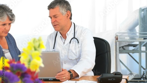 Doctor with his patient looking at the laptop