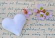Weißes Herz und Blüten auf Handschrift