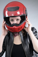 young person preparing her red helmet