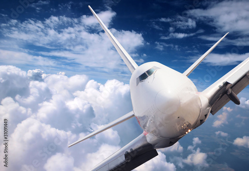Fototapeta Big jet plane above clouds