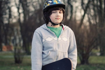 Young happy boy with skateboard, outdoors, steadicam shot