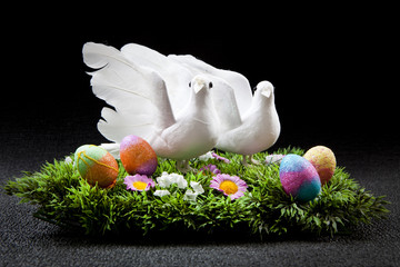 two doves on colorful field with easter eggs