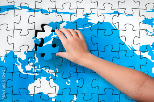 Child's hand inserting piece of jigsaw puzzle into the map hole