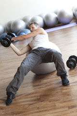 A man lifting weights on stability ball