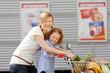 mutter und tochter schieben einkaufswagen vor dem supermarkt
