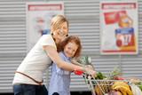 Fototapety mutter und tochter schieben einkaufswagen vor dem supermarkt