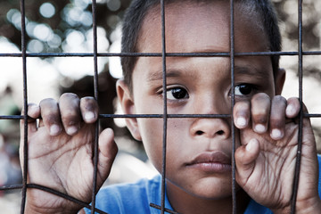 Asian boy against fence - sad expression looking to side