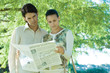 Couple standing outdoors, reading newspaper