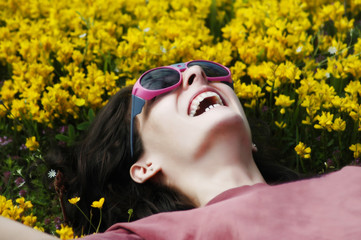 Beautiful young girl with sunglasses laying on yellow flowers