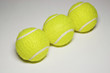 Three tennis balls in a row, close-up