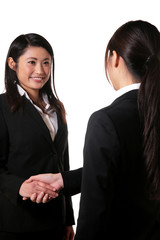 握手をするスーツの女性二人