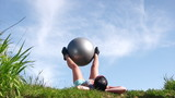 Young attractive woman doing morning sports exercises with ball