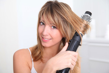 Beautiful blond woman curling her hair