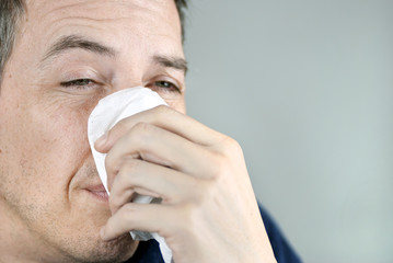 Man Holding Tissue On Nose