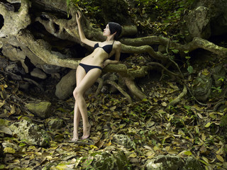 Young brunette beauty in a tropical forest