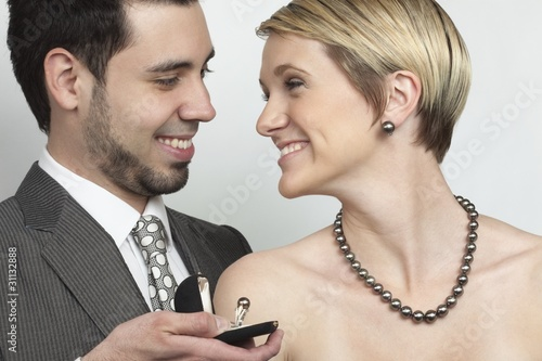 Beautiful woman wearing luxury jewellery, while the man presents an exclusive ring. The necklace is a south sea pearl necklace.