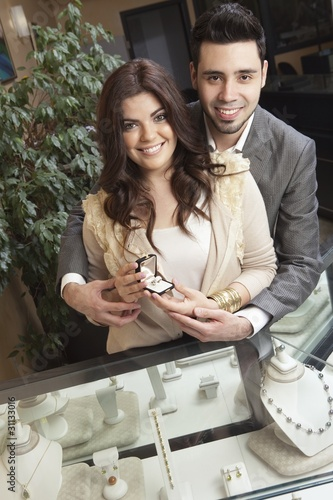 A couple in a jewellery shop holding a luxurious, exclusive ring