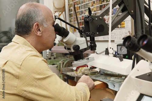 Jeweller working on gem stone to cut and polish and make exclusive jewellery designs