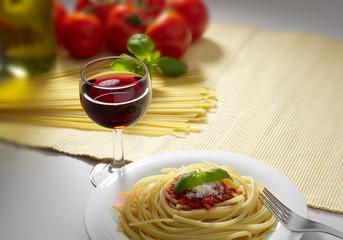 piatto di spaghetti al pomodoro con bicchiere di vino rosso