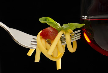 forchetta con spaghetti e bicchiere di vino su fondo nero