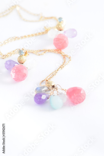 Gold chain and colored earrings on white background
