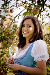 Lachendes Mädchen mit Glas vor Apfelbaum