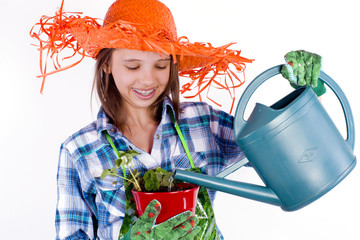 jeune fille qui arrose son plant de fraisier