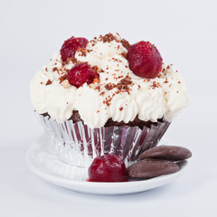 Muffin in a container with whipped cream, cherries and crumbs