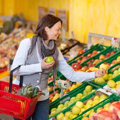 frau kauft äpfel in der obstabteilung
