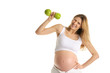 pregnant woman is engaged in fitness dumbbells from apples