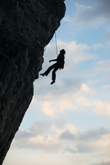 Silhouette of rock climber going down after reaching the top